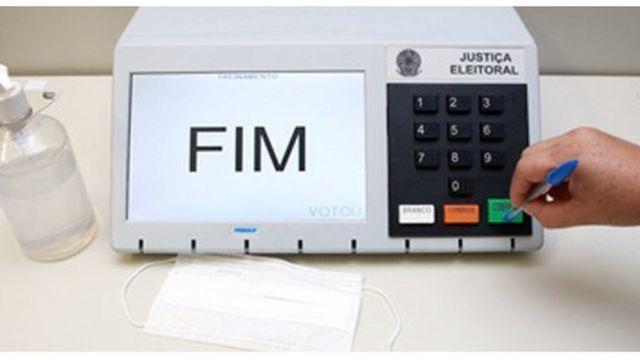 Pressione o botão de confirmação na urna eleitoral eletrônica com uma caneta de mão