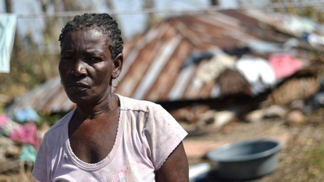 Una mujer haitiana con su casa en ruinas al fondo.