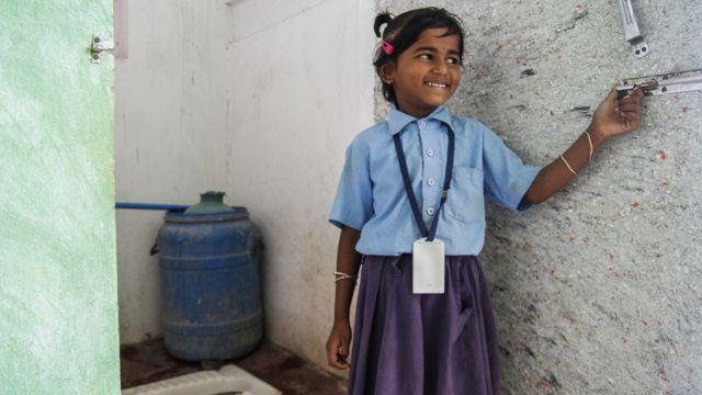 Uma menina na índia do lado de fora de um banheiro com vaso instalado pela WaterAid
