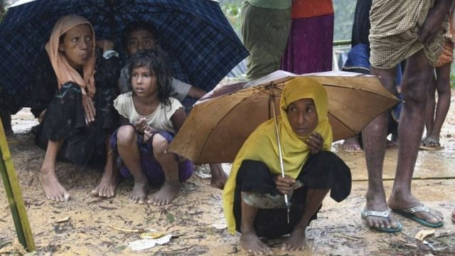 Rohingya Muslim refugees protect themselves from rain in Balukhali refugee camp near the Bangladesh town of Gumdhum on 17 September 2017.