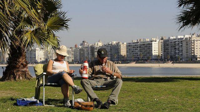 Dos personas toman mate en la rambla de Montevideo.