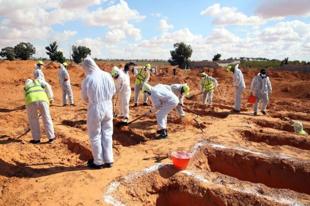 Men in white protection suits digging up bodies of the dead