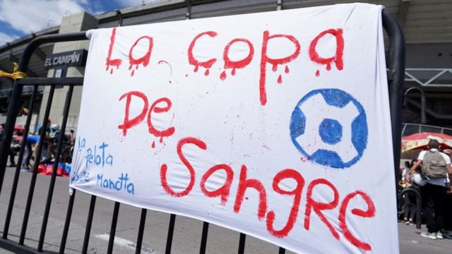 Cartaz pendurado em portão de estádio diz em espanhol: 'La copa de sangre'