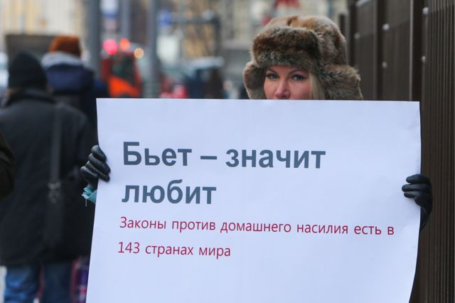 """A demonstrator pickets the Russian parliament quoting the saying, """"If he beats you it means he loves you"""" - underneath the placard points out that 143 countries have a law on domestic violence"""
