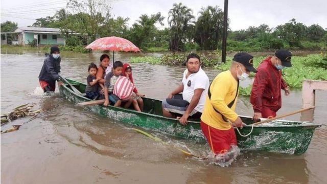 Bomberos rescatan una familia en Honduras por la crecida del río.