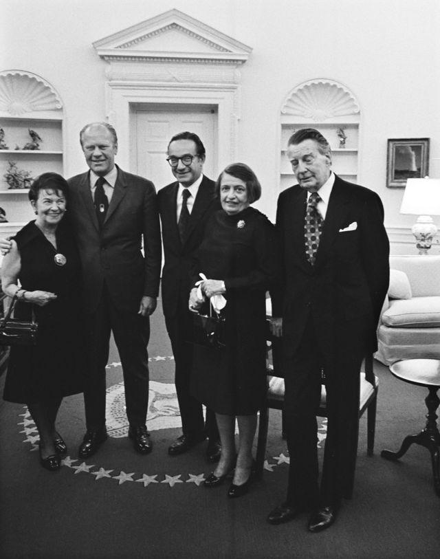 رُز گلدسمیت مادر آلن گریناسپن، جرالد فورد رئیس جمهور آمریکا، آلن گریناسپن آین رند و شوهرش چارلز فرانسیس اُکانر در دفتر بیضی کاخ سفید، 1974