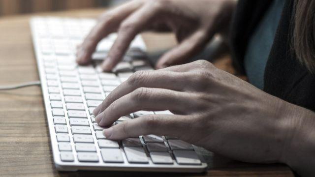 Mujer escribiendo en computador.