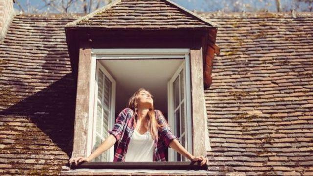 Mulher respirando na janela