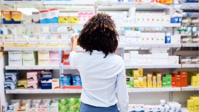 Mulher escolhe remédio em farmácia