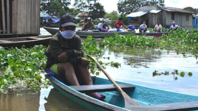 Joven con una mascarilla, sentado en una canoa en Leticia, Colombia