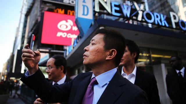 2014年,微博在纳斯达克上市,CEO曹国伟在纽约时代广场拍照