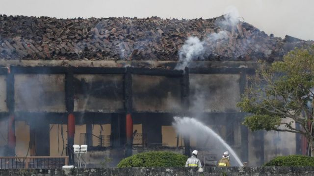 Firefighters try to extinguish a fire at Shuri Castle