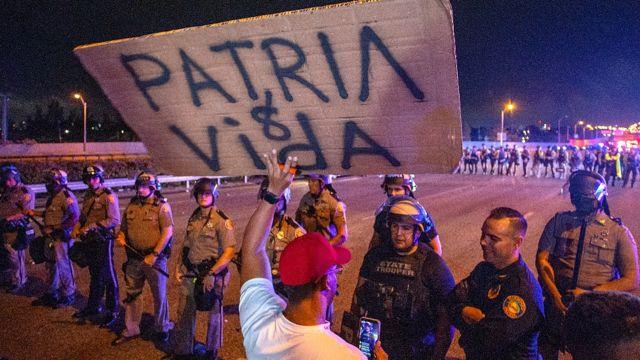 Un manifestante con un cartel en el que se lee Patria y Vida frente a una fila de policías
