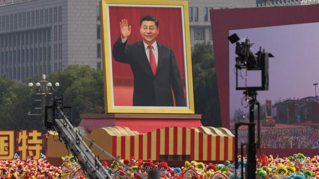 A float with a giant portrait of Chinese President Xi Jinping passes by Tiananmen Square