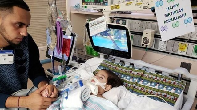 الأب بجانب سرير ابنه عبد الله حسن
