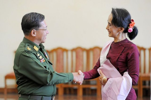 El comandante en jefe de Myanmar, Min Aung Hlaing, le estrecha la mano y le sonríe a Aung San Suu Kyi en Naypyidaw el 2 de diciembre de 2015.