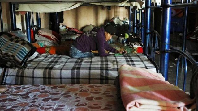A migrant sits on a bed in El Buen Samaritano shelter in Ciudad Juarez