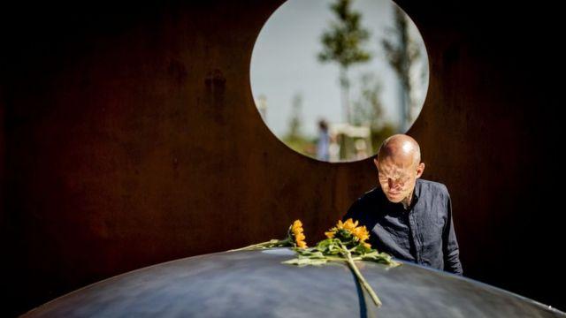 Мужчина в скорби кладет подсолнухи на мемориал