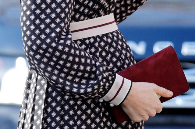 Duchess Catherine clasps a Kate Spade bag against her baby bump in November 2017