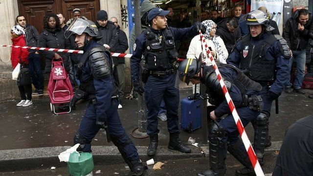 French police secure the area after a man was shot dead outside a police station