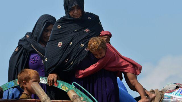 Dos mujeres intentan subir con un niño a un camión con sus pertenencias