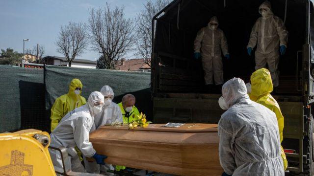 Люди в защитных костюмах держат гроб