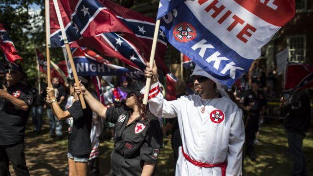 Manifestantes do KKK levantam bandeiras de supremacia branca