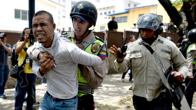 Un funcionario de la Policía Nacional Bolivariana detiene a un manifestante.