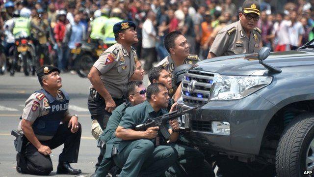 Police crouching behind vehicle