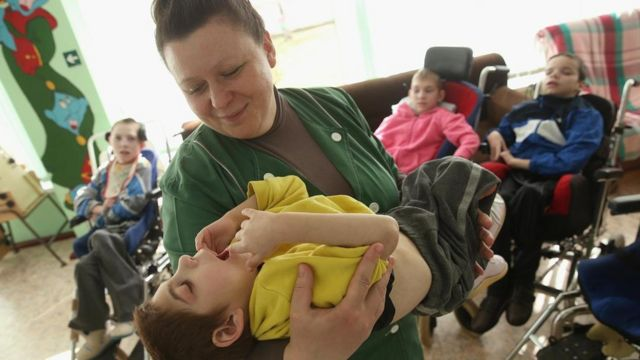 Una mujer sostiene a un niño con problemas motrices.