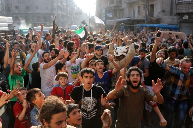 Syrians gather in a street in the northern city of Aleppo in celebrations after rebels said they have broken a government siege