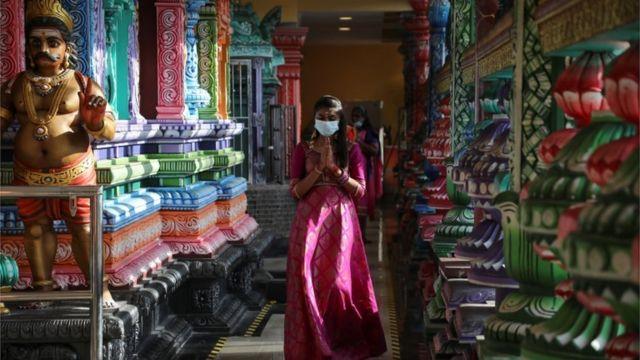 मास्क लगाएर मन्दिरभित्र प्रवेश गर्दै मलेशियाको क्वाल लाम्पुरस्थित एउटा मन्दिर