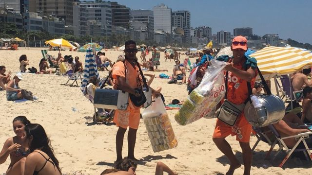 dois vendedores de mate na praia