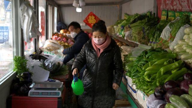 продавщица дизенфицирует овощи