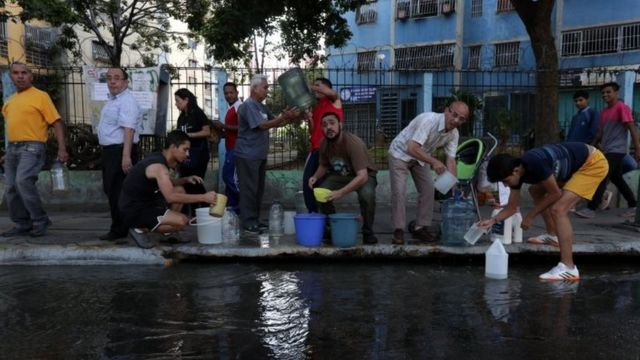 A group of people try to collect water at the sewer system due to shortage of water due to the power outage in Caracas, Venezuela, 12 March 2019. D