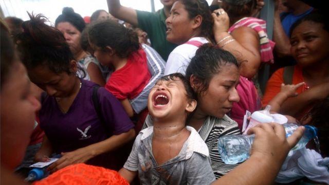 Niño llora en medio de la multitud en la frontera entre Guatemala y México.
