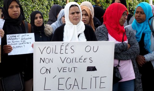 """Demonstrators outside a school in south-western France hold a placard reading: """"Veiled or not veiled, we want equality"""" (28 May 2019)"""