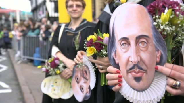 A Shakespeare mask being held at the Stratford carnival