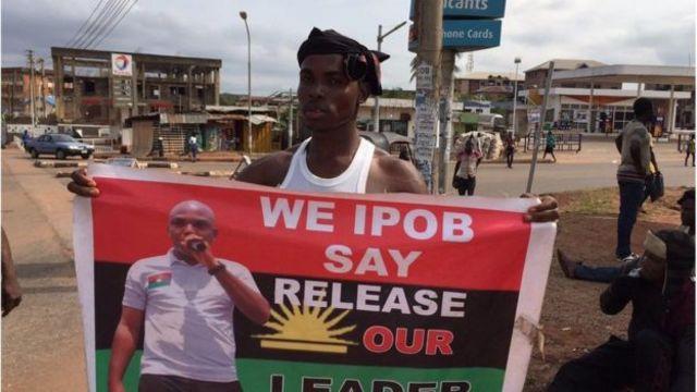 Hombre sostiene un cartel que pide la liberación de un preso en Nigeria.