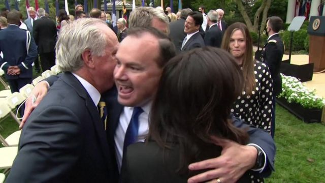 Mike Lee, centre, hugging other attendees at a Rose Garden event