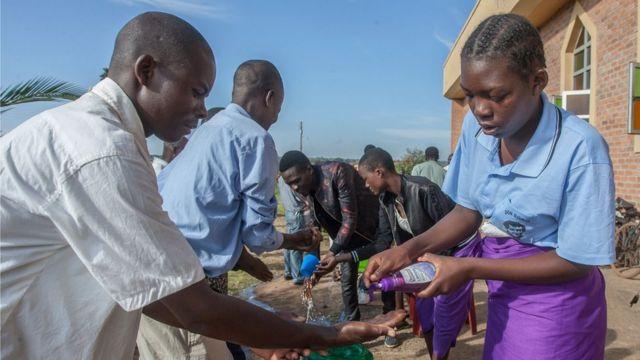 Dos personas lavándose las manos en Malawi.