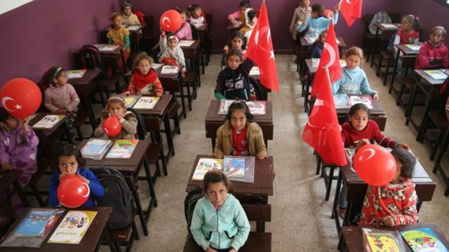 Syrian school children are seen at their classroom al-Caviz village with Turkish flags and balloons