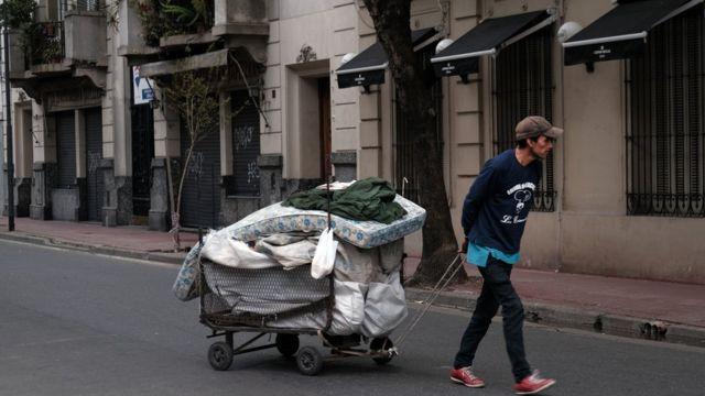 Homem anda com colchão e pertences pelas ruas de Buenos Aires