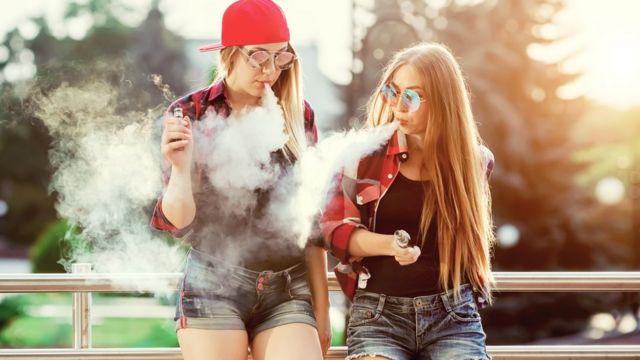 Jovens fumando cigarro eletrônico