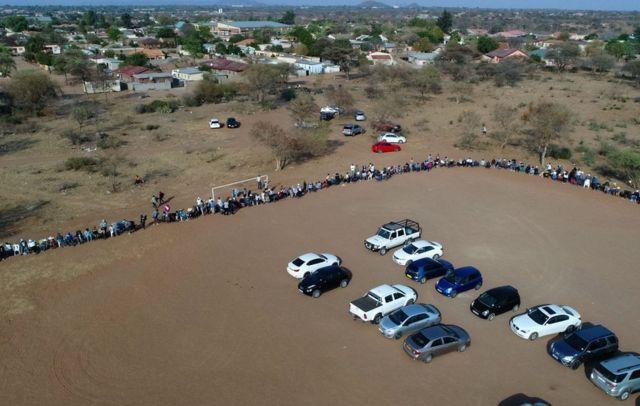Une photo aérienne montre des électeurs en file d'attente pour s'acquitter de leur devoir civique dans un bureau de vote à Gaborone le 23 octobre 2019. - Les élections générales ont lieu au Botswana le 23 octobre 2019.