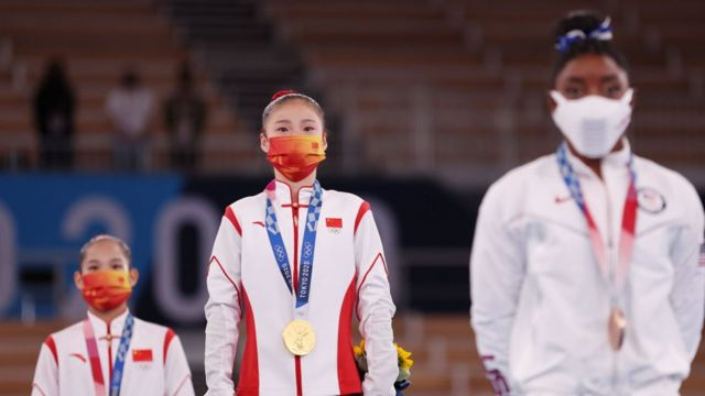 A medalhista de ouro Chenchen Guan da Team China observa durante a cerimônia de medalha final da trave de equilíbrio de ginástica feminina com a atleta norte-americana Simone Biles à sua esquerda