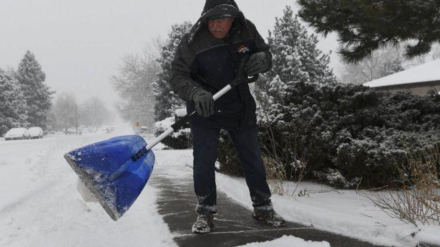 Un hombre sacando nieve en Denver, Colorado.