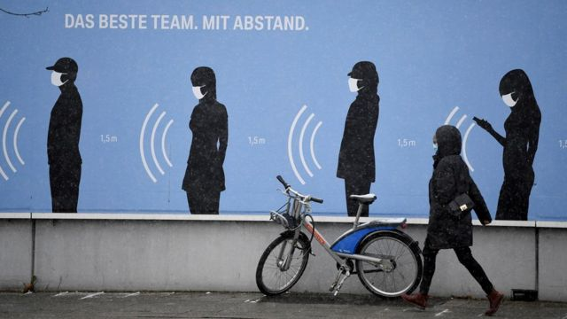 Uma mulher caminha ao lado de uma propaganda na Alemanha com os dizeres: 'O melhor time. Com distância'