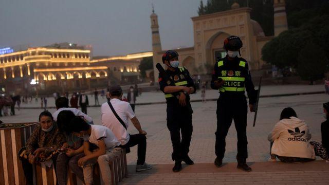 Personas descansando fuera de la mezquita de Aitigar en Kashgar, Xinjiang y la policía haciendo guardia (5/3/2021)
