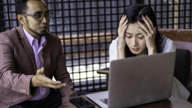Femme stressée discutant avec un collègue devant un ordinateur.